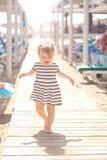Baby walking along wooden walkway Stock Photos