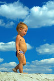 Baby walking on beach at the cloudy sky background Royalty Free Stock Image