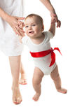 Baby walking holding hands mother, white background. Toddler baby boy walking holding hands mother, white background with a red ribbon Royalty Free Stock Images