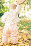 Baby walking and holding her mother hand outdoor Stock Image