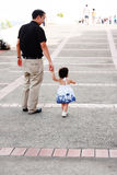 Baby walking like a model with her father Stock Photo