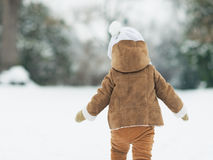 Baby walking in winter park . rear view Stock Image