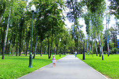 Baby walks alone on the footpath in the city park Royalty Free Stock Photos