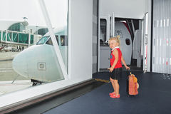 Baby walks for boarding to flight in airport departure gate Stock Photos