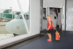 Baby walks for boarding to flight in airport departure gate. Little baby girl walks for boarding to flight in departure gate from airport transit hall and stock image