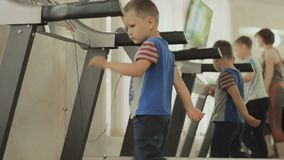 The baby walks on the treadmill in the GYM. The baby walks on the treadmill. the kid is exercising in the gym near the mirror. Boy cares about his body, figure stock video