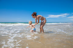 Baby want waves with mother Royalty Free Stock Image
