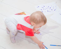 The baby was covered in watercolors and spilled water. In a puddle of water sits covered in paint by a child stock photos