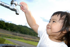 Baby wash hand and turn off faucet in the outdoor. She is a happy baby washing her hand and turn off faucet in the outdoor Royalty Free Stock Images