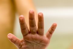 The baby washes in the bathroom. Wet hand, wrinkled skin from water stock photos