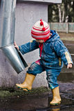Baby washes the feet of a drain pipe. Royalty Free Stock Photo