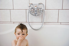 Baby washing in the bath. He holding nose and start diving under Royalty Free Stock Image