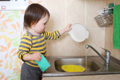 Baby washing dishes Royalty Free Stock Image