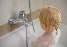 Baby washing in foamy bathtub Royalty Free Stock Photo