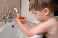 Baby washing hand in bathroom Stock Images