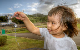 Baby washing her hand in the outdoor stock images