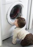 Baby and washing machine Stock Image