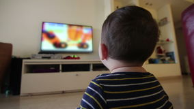 Baby watching blurred content on TV. Shot containing of Young child watch TV stock video