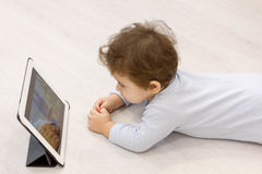 Baby watching cartoons on her tablet computer in the background of the toys he child does not want to play Stock Image