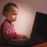 Baby is watching computer Stock Image