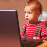 Baby is watching computer Stock Images