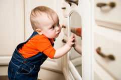 Baby watching inside kitchen oven Royalty Free Stock Images