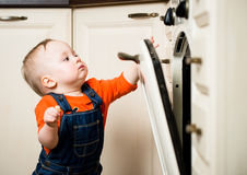 Baby watching inside kitchen oven Stock Images
