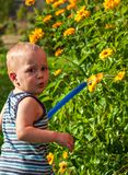 Baby is watering the flowers Royalty Free Stock Images