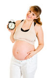 Baby on way! Pregnant holding alarm clock Royalty Free Stock Photography