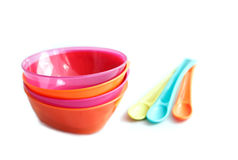 Baby weaning bowls with the spoons on a white back Stock Photos