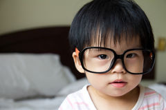 Baby wear eye glasses. Portrait of a baby girl wearing big spectacles Stock Photo