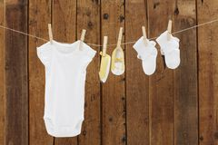 Baby wear hanging in clothespins. Babygro and booties against wooden background stock photos