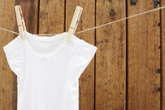 Baby wear hanging in clothespins on washing line. Babygro hanging on washing line against wooden background stock photos