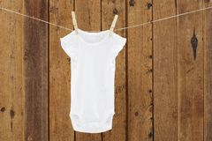Baby wear hanging in clothespins on washing line. Babygro hanging on washing line against wooden background royalty free stock image