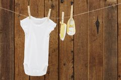 Baby wear hanging in clothespins on washing line. Babygro and booties against wooden background royalty free stock photos