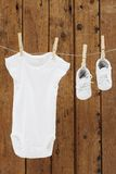 Baby wear hanging in clothespins on washing line. Babygro and booties against wooden background royalty free stock images