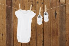 Baby wear hanging in clothespins on washing line. Babygro and booties against wooden background stock image