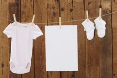 Baby wear hanging in clothespins on washing line. Babygro and socks and blank page on washing line royalty free stock photography