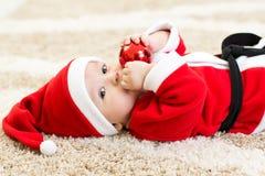 Baby weared hollding Weihnachtsball Sankt lizenzfreies stockbild