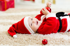 Baby weared hollding Weihnachtsball Sankt lizenzfreies stockfoto