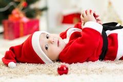 Baby weared Sankt, die nahe Weihnachtsbaum liegt stockfoto