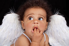 Baby Wearing Angel Wings. An adorable baby with an innocent look wearing white angel wings and sitting against a black background Royalty Free Stock Photography