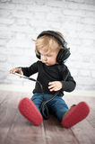 Baby wearing big black headphones Stock Photography