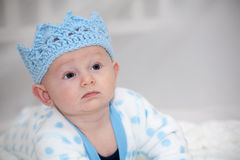 Baby Wearing Blue Knit Crown. Baby with blue eyes lying on his back looking to the side with a thoughtful and stern expression wearing a light blue knit crown Royalty Free Stock Photography