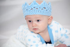 Baby Wearing Blue Knit Crown. Baby with blue eyes lying on his stomach looking to the side with happy expression wearing a light blue knit crown hat playing king Stock Photography