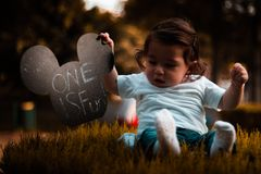 Baby Wearing Blue Shirt Holding Mickey Mouse Head Cutout Sitting on Grass royalty free stock image