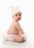 Baby wearing bunny costume. Cute baby girl wearing bunny rabbit ears and tail Easter costume, isolated on white Royalty Free Stock Photo