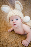 Baby Wearing Bunny Outfit. Baby in knit hat with bunny ears and fluffy bunny tail. A fun idea for a knit or crochet craft outfit for Easter or Halloween Royalty Free Stock Image