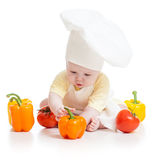 Baby wearing a chef hat with healthy food. Vegetables stock photos