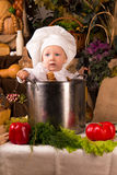 Baby wearing a chef hat inside a cooking stock pot. Portrait of a baby wearing a chef hat sitting inside a large cooking stock pot surrounded by vegetables and Stock Image